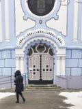 Mujer que camina delante de la pequeña iglesia azul Foto de archivo libre de regalías