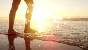 Mujer que camina descalzo en el océano en la arena contra la sol en el océano stock de ilustración