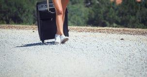 Mujer que camina en el camino con equipaje Imagen de archivo