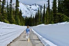 Mujer que camina en el camino con las paredes de la nieve fotos de archivo libres de regalías