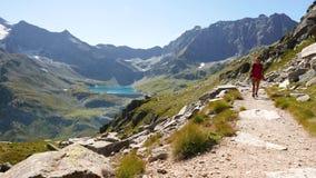Mujer que camina en el sendero en paisaje idílico de la montaña con el lago azul, el pico de alta montaña y el glaciar Aventuras  almacen de video