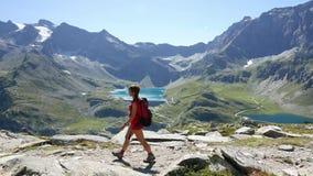 Mujer que camina en el sendero en paisaje idílico de la montaña con el lago azul, el pico de alta montaña y el glaciar Aventuras  metrajes