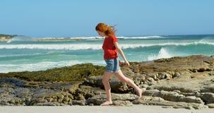 Mujer que camina en la costa costa rocosa 4k almacen de metraje de vídeo
