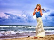 Mujer que camina en la playa cerca del océano con las ondas Imagenes de archivo