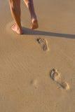 Mujer que camina en la playa de la arena que deja huellas en la arena Foto de archivo libre de regalías