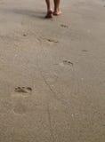 Mujer que camina en la playa de la arena que sale de huellas Imagen de archivo libre de regalías