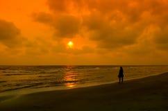 mujer que camina en la playa el tiempo de la puesta del sol Fotos de archivo libres de regalías