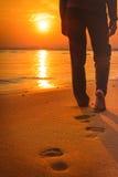 Mujer que camina en la playa en la puesta del sol que deja huellas Imagen de archivo libre de regalías