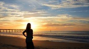Mujer que camina en la playa en la salida del sol Imágenes de archivo libres de regalías