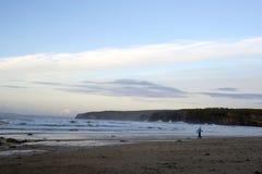 Mujer que camina en la playa fría rocosa imagenes de archivo