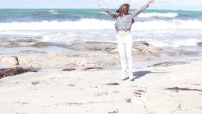 Mujer que camina en la playa por el mar almacen de video