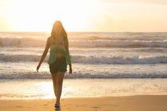 Mujer que camina en la playa, sol en el mar del verano de la mañana Fotos de archivo libres de regalías