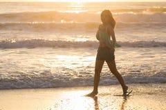 Mujer que camina en la playa, sol por la mañana Fotos de archivo