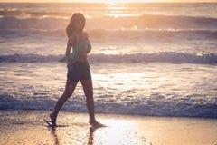Mujer que camina en la playa, sol por la mañana Imagen de archivo libre de regalías