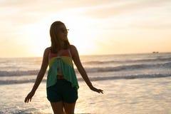 Mujer que camina en la playa, sol por la mañana Imagenes de archivo