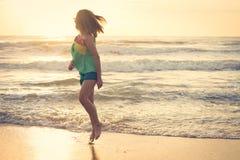 Mujer que camina en la playa, sol por la mañana Imagen de archivo