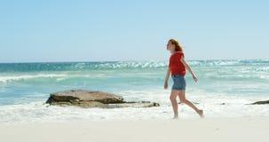 Mujer que camina en la playa en un día soleado 4k almacen de metraje de vídeo