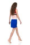 Mujer que camina en Mini Dress And High Heels opinión de lado trasero imagenes de archivo