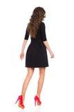 Mujer que camina en Mini Dress negro, vista posterior Foto de archivo libre de regalías