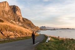 Mujer que camina en un camino en Lofoten Imagen de archivo libre de regalías