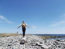 Mujer que camina en una conexión de la madera de deriva la playa fotos de archivo libres de regalías