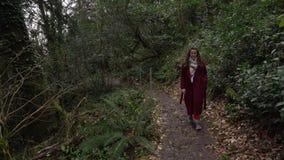Mujer que camina en una trayectoria en el bosque verde de la arboleda del tejo-boj en Sochi, Rusia almacen de metraje de vídeo