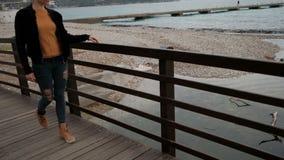 Mujer que camina en una verja del puente de madera y tocada sus fingeres metrajes