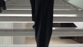 Mujer que camina encima de la escalera blanca en el hotel metrajes