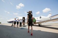Mujer que camina hacia Jet At Airport privada Imagen de archivo libre de regalías