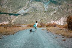 Mujer que camina a las montañas con los perros foto de archivo