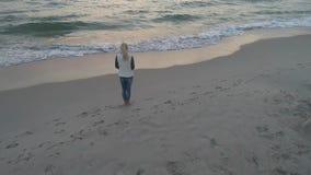 Mujer que camina a lo largo de la playa almacen de video