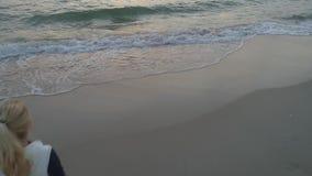 Mujer que camina a lo largo de la playa metrajes