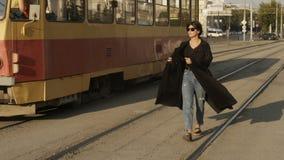 Mujer que camina a lo largo de los carriles de la tranvía almacen de metraje de vídeo