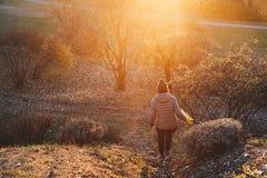 Mujer que camina a lo largo de una trayectoria con la flor en su mano - trave feliz Foto de archivo libre de regalías
