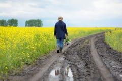 Mujer que camina a lo largo del camino con un ramo de lilas Foto de archivo libre de regalías