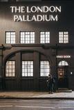 Mujer que camina más allá de la entrada de la etapa al teatro de Londres Palladium, Londres, Reino Unido imágenes de archivo libres de regalías