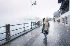 Mujer que camina mientras que nieva Imagen de archivo libre de regalías