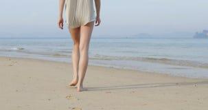 Mujer que camina para regar en la playa, vista posterior trasera de la chica joven almacen de metraje de vídeo
