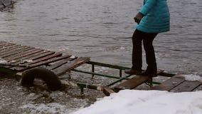 Mujer que camina peligroso en un embarcadero helado destruido almacen de metraje de vídeo