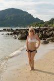 Mujer que camina solamente en la playa en vestido azul Foto de archivo libre de regalías