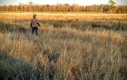 Mujer que camina a través de campo abierto Imagen de archivo