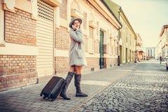 Mujer que camina a través de la calle con la maleta mientras que habla encendido fotografía de archivo libre de regalías
