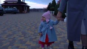 Mujer que camina a un pequeño bebé lindo en invierno almacen de metraje de vídeo