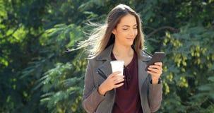 Mujer que camina usando un teléfono y que lleva a cabo una bebida