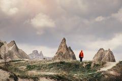 Mujer que camina y que disfruta de paisaje de la montaña de Cappadocia imagenes de archivo