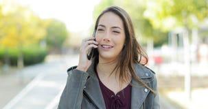 Mujer que camina y que habla en el teléfono en un parque