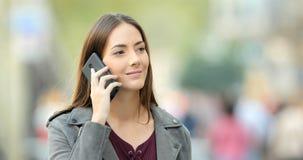 Mujer que camina y que invita al teléfono en la calle