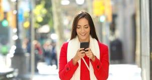 Mujer que camina y que manda un SMS en el teléfono en la calle