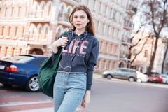 Mujer que camina y que escucha la música del smartphone en ciudad Fotografía de archivo libre de regalías