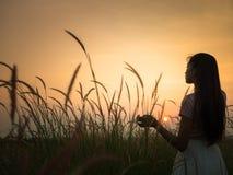 Mujer que camina y que restaura en un prado en la puesta del sol imagen de archivo